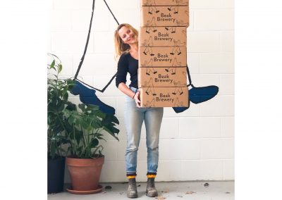 beak brewery lady carrying stack of crates boxes